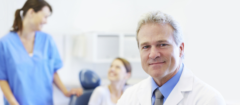 A mature dentist crossing his arms as his assistant and patient converse in the background